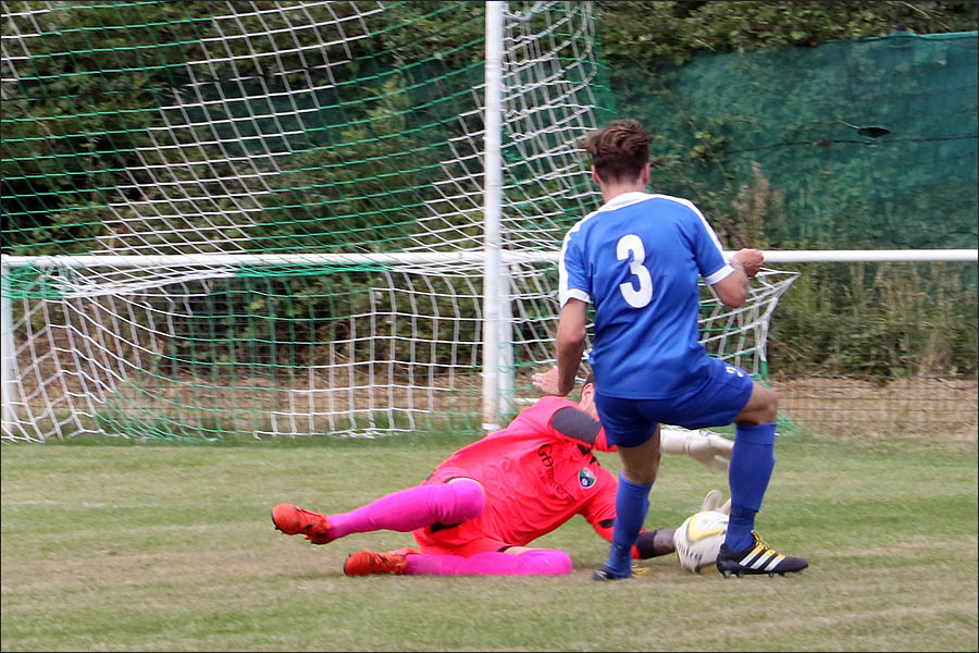 The Colney Keeper dives bravely to deny tom Inch