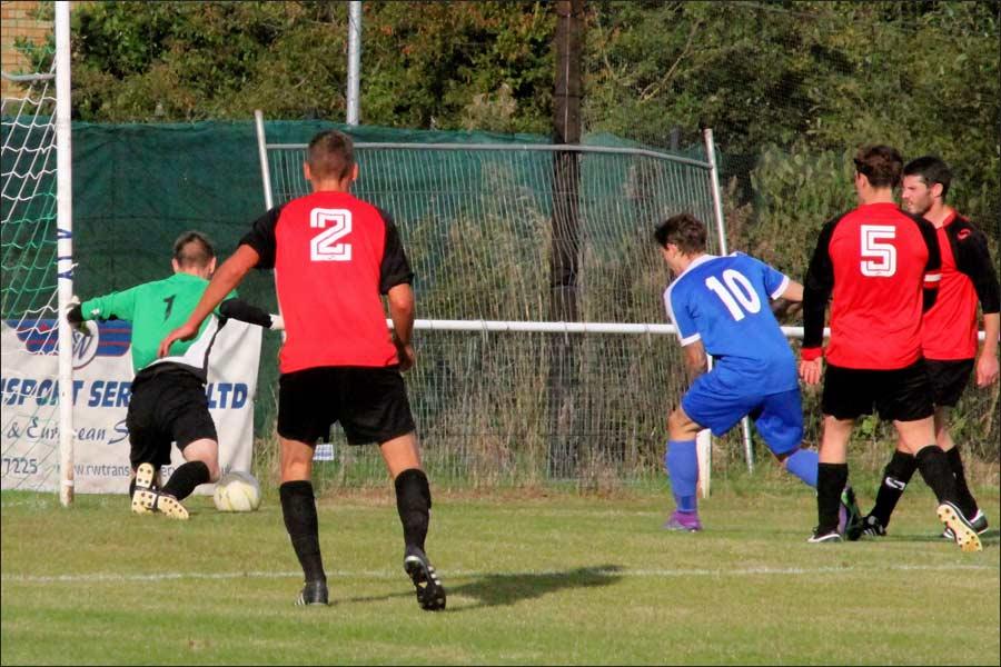 Luke Wells beats the keeper but his shot hits the post